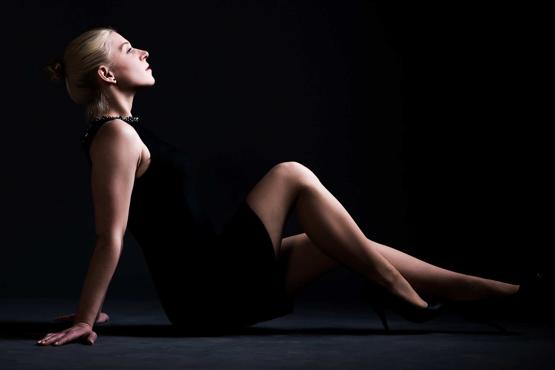 blonde beauty with high heels and directional light sitting on the floor in a reclining position