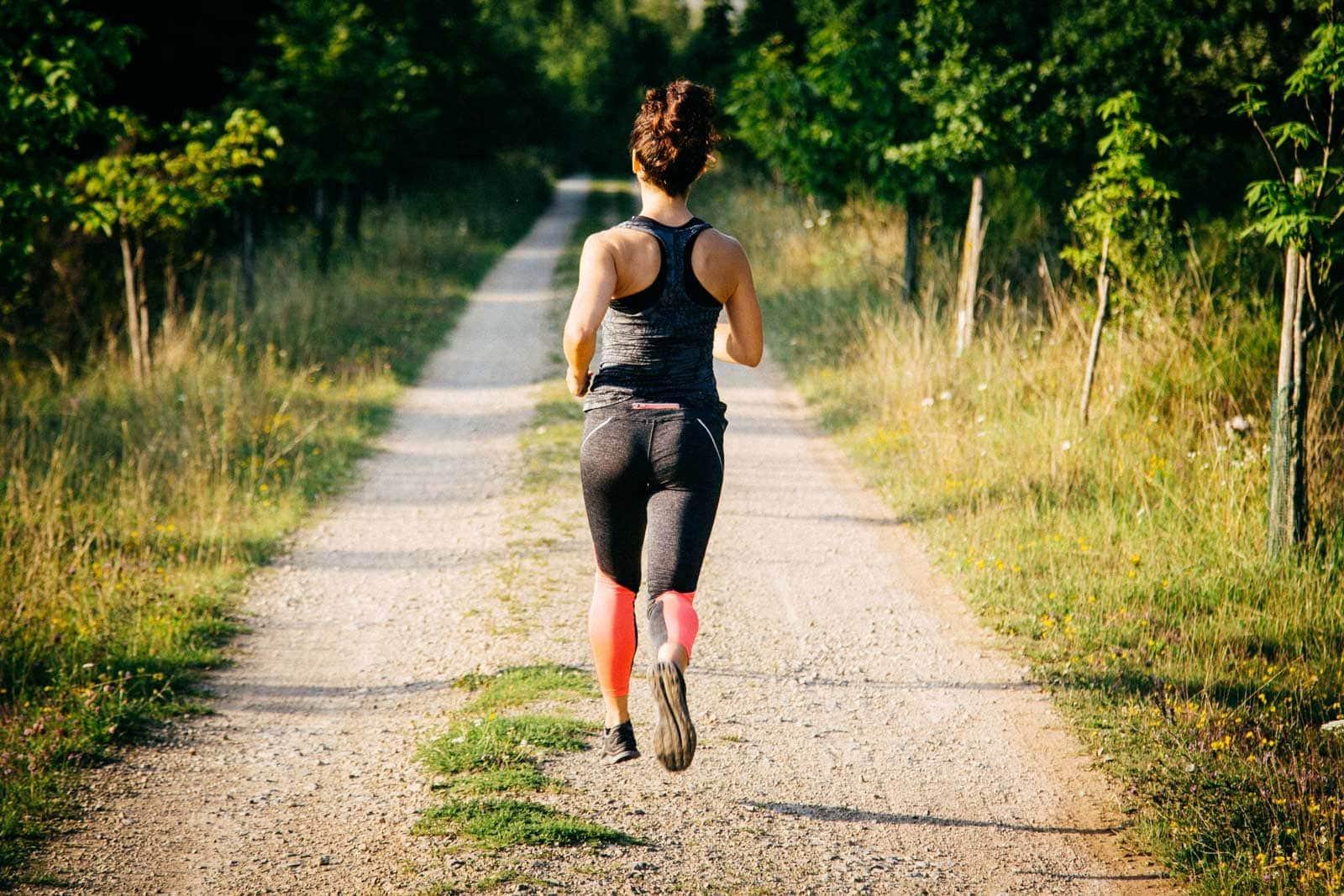 Hinteransicht einer sportlich gekleideten Frau beim Laufen am Rande des Mattheiser Walds