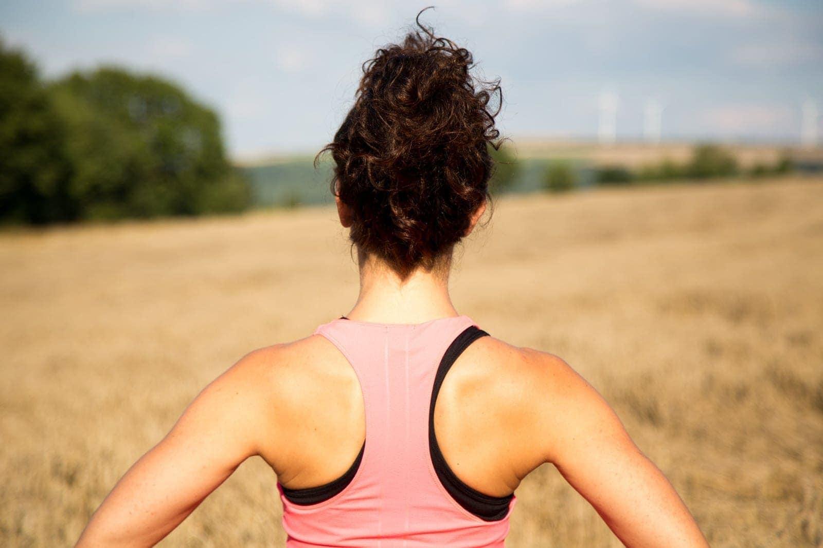 Hinteransicht einer Frau in Sportkleidung vor einem Kornfeld