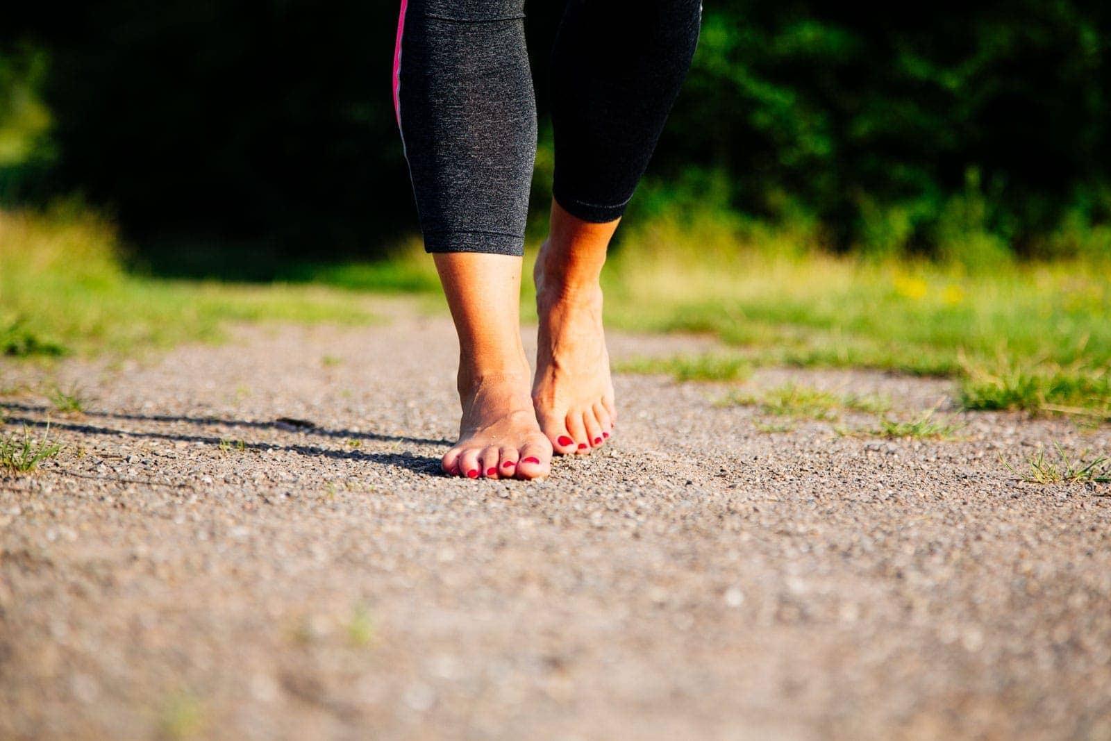 Fotografie einer auf steinigem Boden gehenden Barfussigen Frau