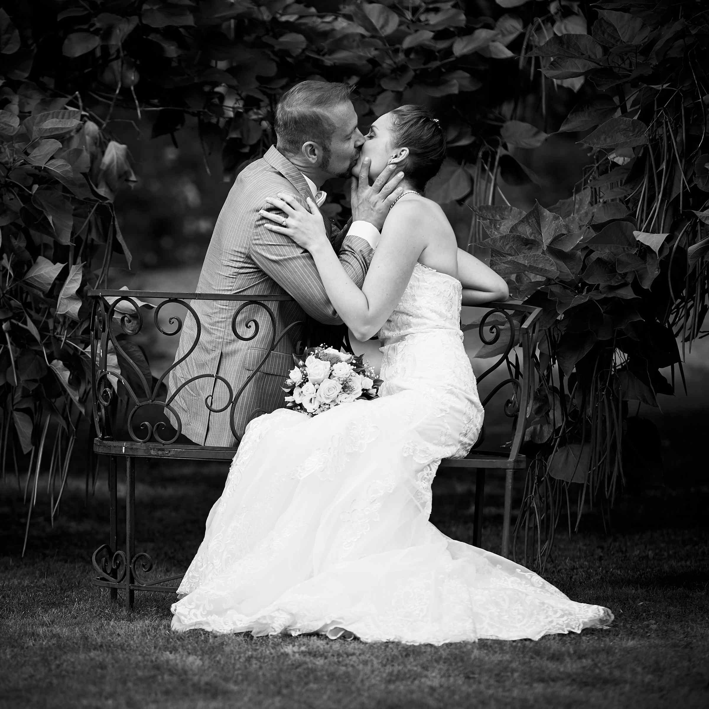 Schwarz Weiß Fotografie eines küssenden Brautpaares im Garten am Weinromantikhotel Richtershof