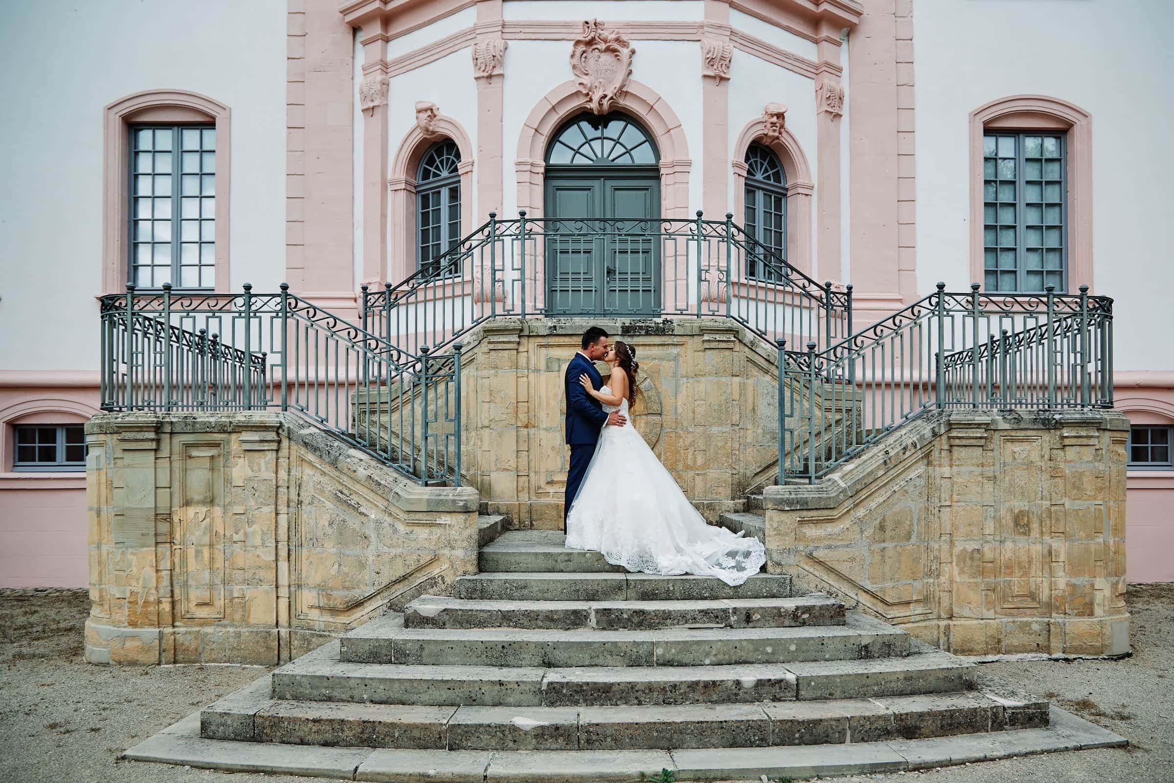 frisch verheiratetes brautpaar vor dem schloss weilerbach