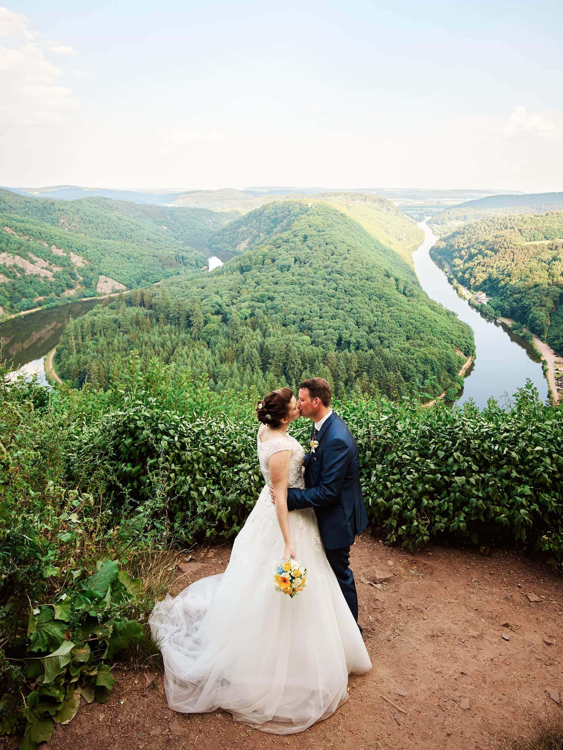 Ein frisch verheiratetes Brautpaar vor der Saarschleife.